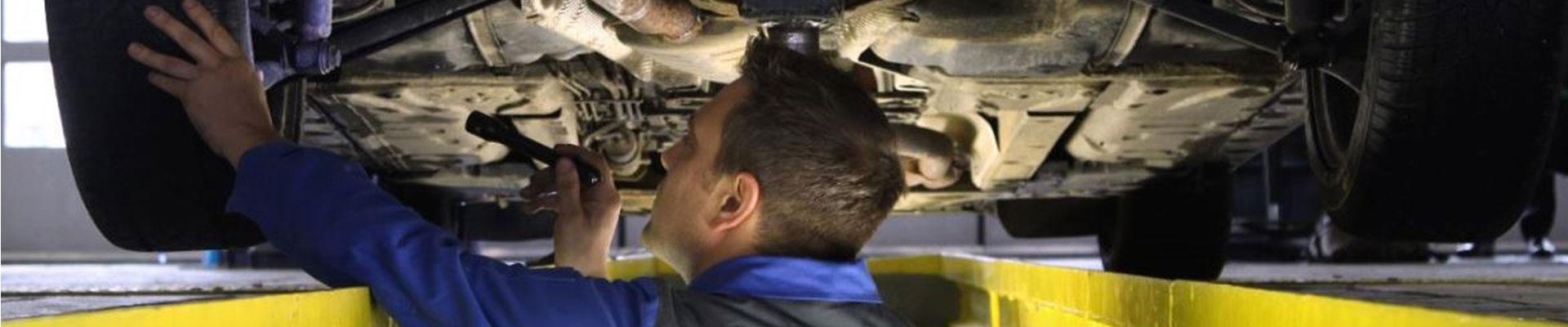 Unterseite eines Autos wird von einem Mechaniker geprüft